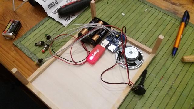MP3-Player, dessen Stromversorgung, Lautsprecher, Lautstärke und angelötete Steuertaster in der endgültigen Anordnung auf dem Boden der Schublade.